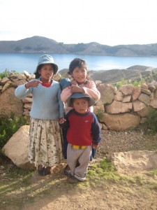 The descendents of Inca's - Andean kids take photos for cash with Lake Titicaca in the background (one of the historic wealth bases of the Inca's)